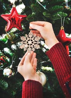 Colocando uma decoração de floco de neve na árvore de natal