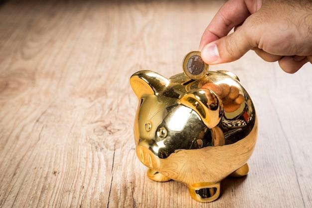 Colocando uma moeda de 1 real em um cofrinho