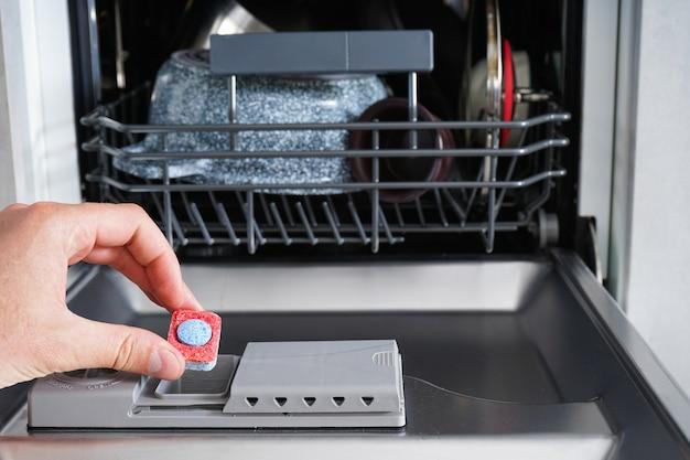 Colocar a aba na máquina de lavar louça e fechar. uma mão de homem segurando a tabuleta de detergente de máquina de lavar louça.