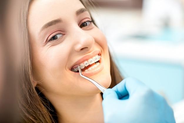 Colocar aparelho dentário nos dentes da mulher no consultório odontológico
