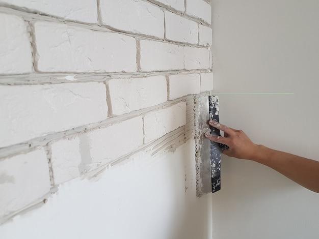 Colocar ladrilhos de gesso em cola de gesso na parede com uma espátula. reparo doméstico.