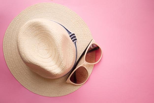 Colocar o chapéu de mulher praia palha com óculos de sol no plano rosa. vista do topo. viagem de verão.