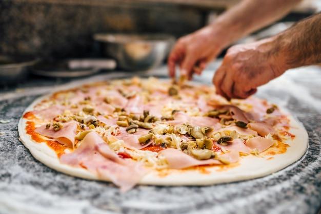 Colocar os ingredientes na pizza.