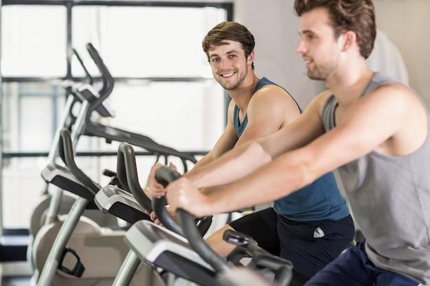 Colocar pessoas fazendo bicicleta ergométrica no ginásio