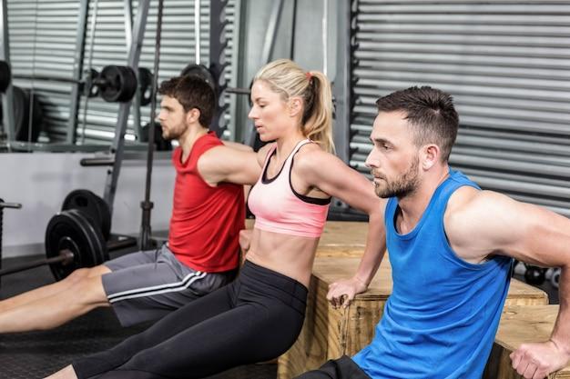 Colocar pessoas fazendo exercícios com caixa no ginásio