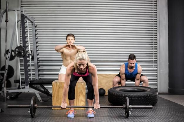 Colocar pessoas fazendo exercícios no ginásio