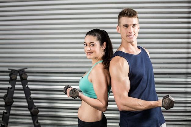 Colocar pessoas levantando halteres de costas no ginásio