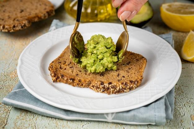 Colocar purê de abacate em uma fatia de pão saudável por duas colheres. abacate rico em gorduras saturadas saudáveis