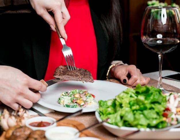 Colocar um pedaço de bife de carne em outro prato de pessoas com salada.