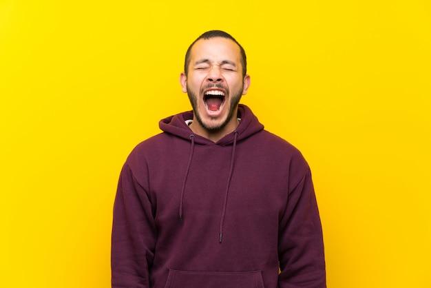 Colombiano, homem, com, sweatshirt, sobre, parede amarela, shouting, para, a, frente, com, boca largo aberto