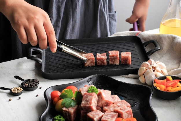Coloque a carne na grelha, a chef feminina prepara a carne em cubos ou saikoro premium wagyu, a carne em mármore cortada em cubos para grelhados, tepanyaki ou yakiniku. foco selecionado