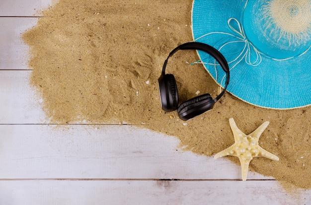 Coloque acessórios de praia para férias planas com fones de ouvido de chinelos de praia e chapéu de praia no verão