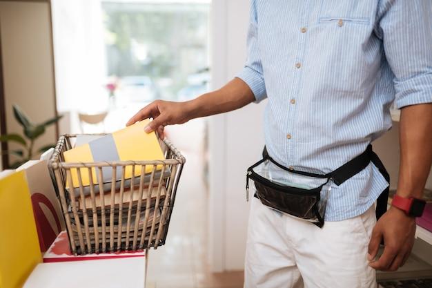 Coloque aqui. jovem assistente de loja segurando a bolsa na cintura enquanto fica em pé perto da estante