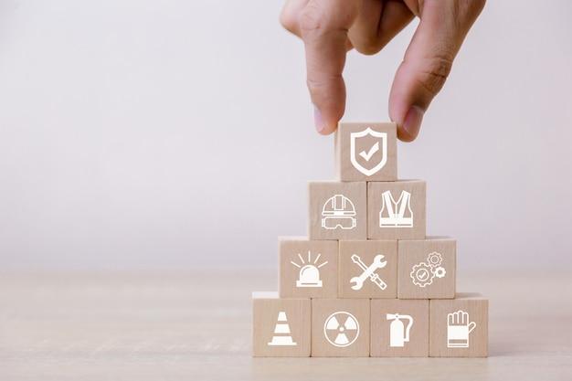 Coloque blocos de madeira na pirâmide. conceito de segurança de trabalho de 100 por cento.