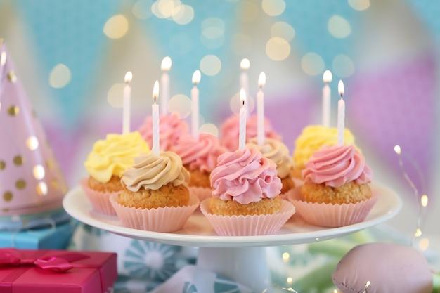 Coloque deliciosos cupcakes de aniversário na mesa