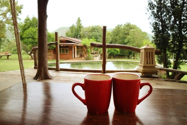 Coloque duas xícaras de café vermelho em uma mesa de madeira.