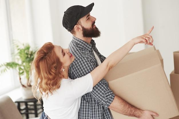 Coloque isso aqui. casal feliz juntos em sua nova casa. concepção de movimento
