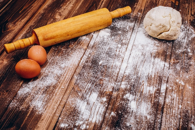 Coloque na mesa de madeira com rolo, massa, ovos e farinha para cozinhar pastagem de natal