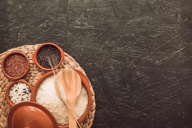 Coloque o tapete com arroz cru em taças diferentes no pano de fundo texturizado