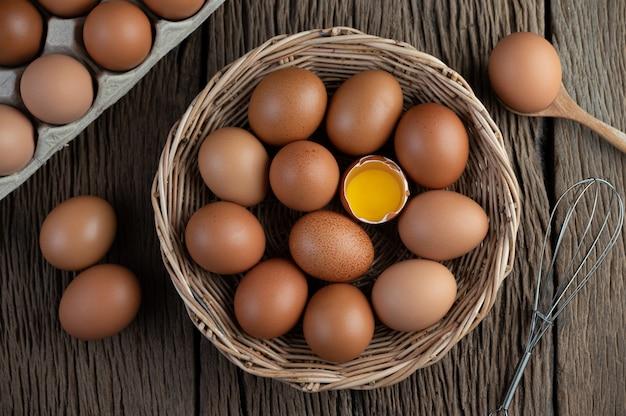 Coloque os ovos em uma cesta de madeira sobre um piso de madeira.