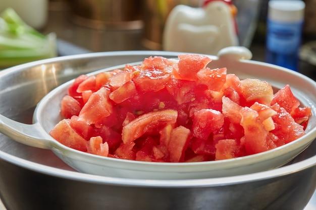 Coloque os tomates picados na peneira para escorrer o líquido, preparando o prato de acordo com a receita.