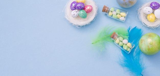 Coloque ovos de páscoa em ninhos e garrafas de vidro em uma cor
