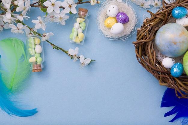Coloque ovos de páscoa no ninho e garrafas de vidro em um azul