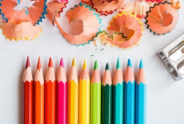 Colora lápis, aparas e um apontador em um branco. acessórios escolares