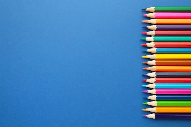 Colora lápis no fundo azul com espaço da cópia para o texto.