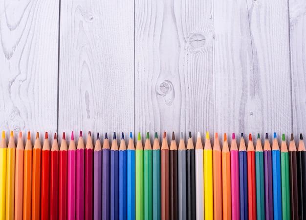 Colora lápis no fundo na madeira branca e cinzenta, fim acima.
