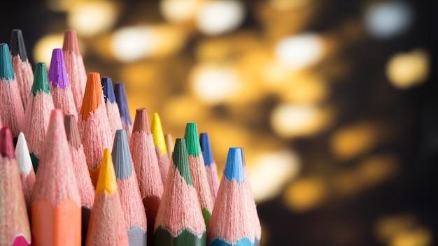 Colora o conceito criativo do sucesso dos lápis no close-up preto do fundo.