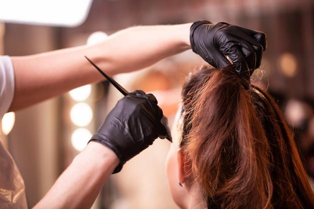 Coloração de cabelo no salão, estilo de cabelo. assistente profissional pinta o cabelo no salão. conceito de beleza, cuidados com os cabelos.