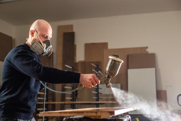 Coloração de madeira com pistola de pulverização branca, aplicação de retardante de chama garantindo proteção contra incêndio, dispositivo de pulverização sem ar, conceito industrial