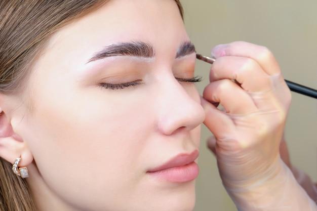 Coloração de sobrancelha. mulher aplicando tonalidade na testa com pincel de maquiagem close-up