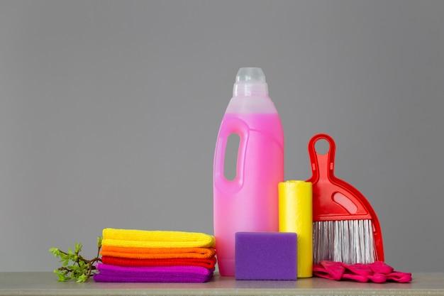 Colorido conjunto de ferramentas para a limpeza da casa e galhos com folhas verdes
