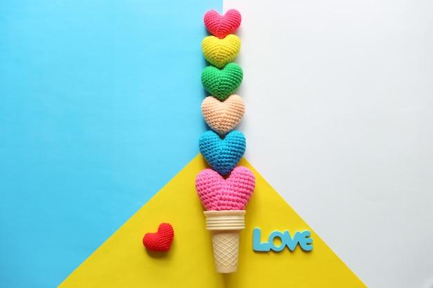 Colorido de coração de crochê artesanal em copo de waffle em fundo colorido para dia dos namorados