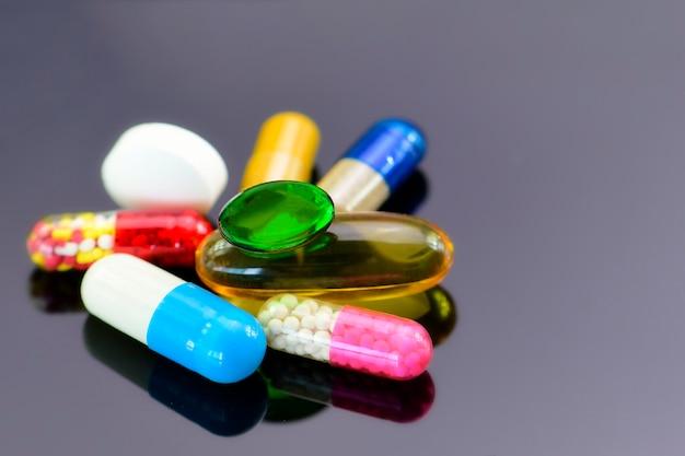 Colorido de medicamentações orais no fundo escuro.