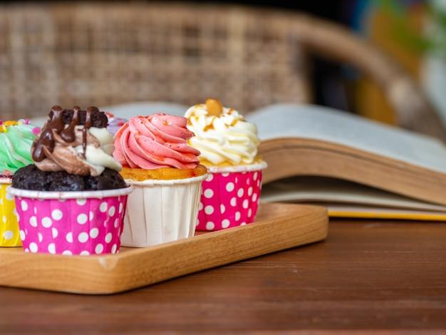 Colorido do queque caseiro na bandeja de madeira sobre e livro aberto na tabela de madeira.