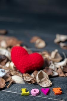 Colorido do texto de madeira do amor com as flores e as folhas secadas aroma.