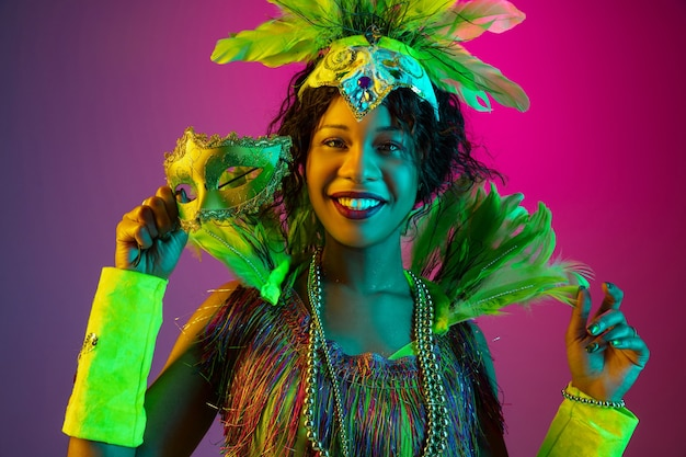Colorido. mulher jovem e bonita no carnaval, elegante traje de máscaras com penas dançando na parede gradiente em neon. conceito de celebração de feriados, tempo festivo, dança, festa, diversão.
