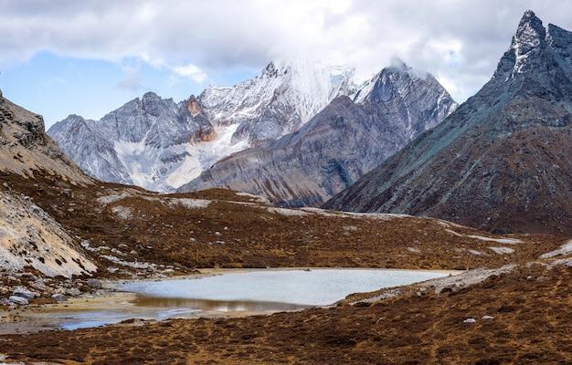 Colorido na floresta de outono e montanha de neve na reserva natural de yading, o último shangri la