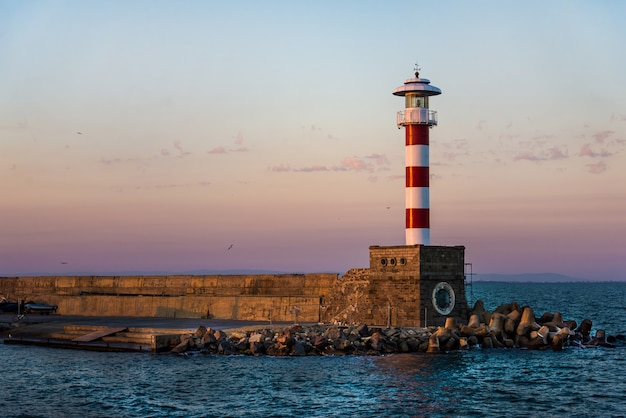 Colorido pôr do sol sobre o farol da costa do mar de bourgas