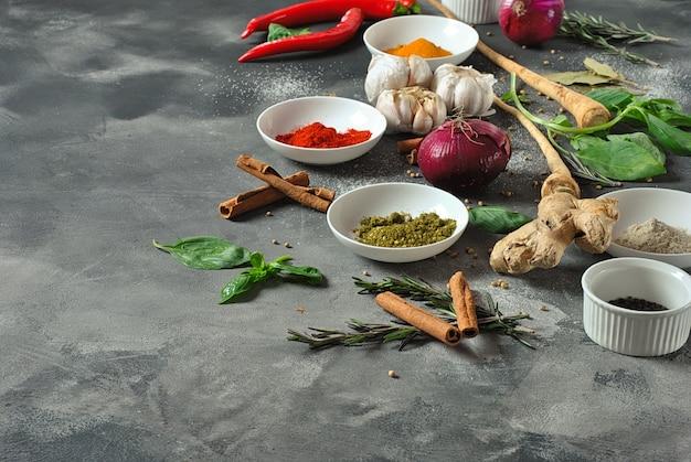 Colorido vários tipos de ervas frescas e secas e especiarias para cozinhar em um fundo escuro