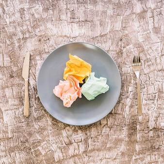 Coloridos, amarrotado, papeis, ligado, prato, entre, garfo, e, faca cozinha, sobre, madeira, superfície