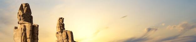 Colossos de memnon luxor tebas contra o pano de fundo do amanhecer no egito