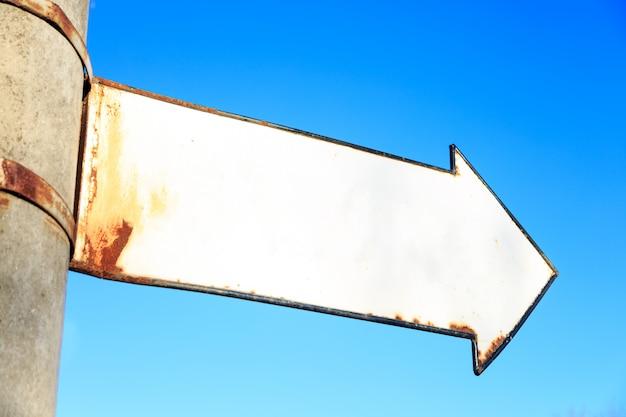 Coluna com placa enferrujada em forma de seta