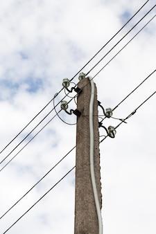 Coluna de concreto com fios metálicos de alta tensão