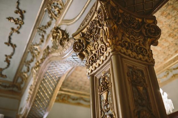 Coluna e capital dentro do cofre de uma igreja decorada no estilo neoclássico.