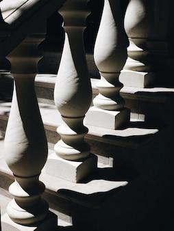 Colunas brancas no corrimão do close-up de escadas com sombra
