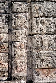 Colunas de pedra cinzeladas com imagens maias em chichen itza, méxico.